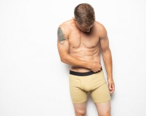 A man wears WAMA hemp boxer briefs and adjusts the hem.
